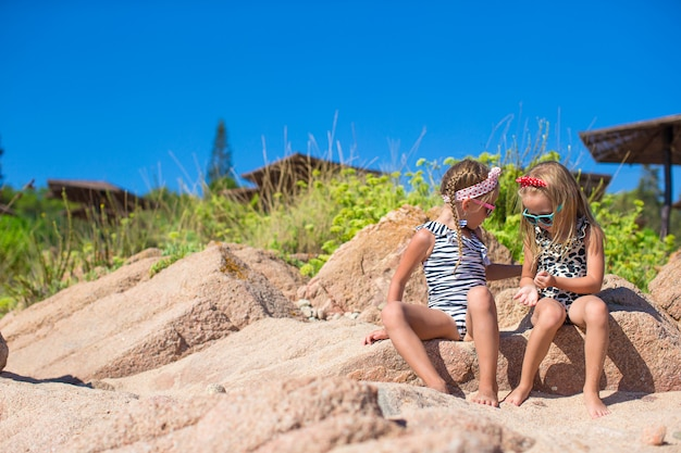 Adorabili ragazze carine si divertono sulla spiaggia bianca durante le vacanze