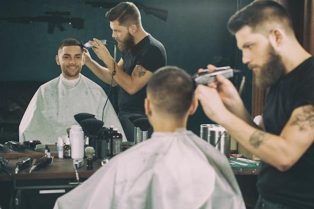 Adorerai la tua nuova pettinatura. mezzo busto di un barbiere che lavora nel barbiere dando un taglio di capelli a un cliente maschio