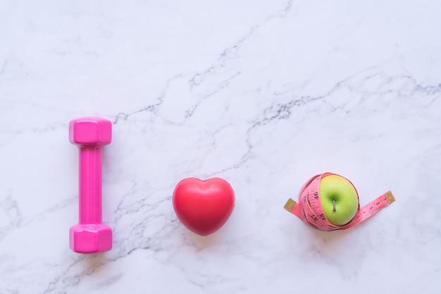 Adoro il concetto di cibo sano, piatta laici di manubri rosa con cuore rosso e mela verde