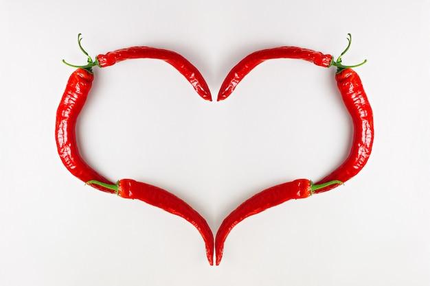 Adoro il peperoncino rosso, a forma di cuore sul tavolo di legno bianco, vista dall'alto