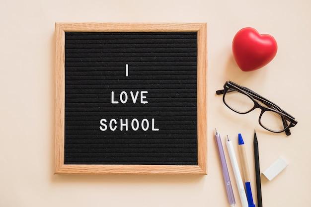 Adoro il testo scolastico su ardesia vicino a penne; gomma per cancellare; occhiali e cuore rosso su sfondo chiaro