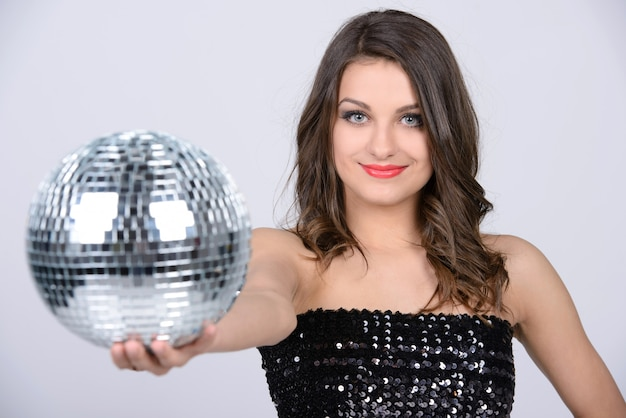 Adoro la musica. signora sexy con sfera da discoteca lucida.