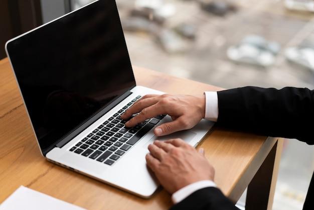 Adulto del primo piano che lavora il suo computer portatile all'ufficio