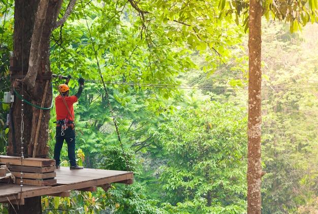 Adventure zipline high wire park - persone in rotta nel casco da montagna e attrezzatura di sicurezza, pronte a scendere su zipline nella foresta, sport estremi
