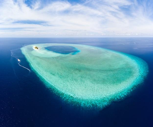 Aeree: vista atollo tropicale dall'alto, barriera corallina blu acqua laguna turchese