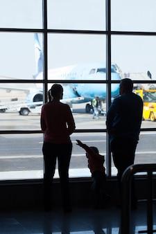 Aerei di sorveglianza della giovane famiglia in un aeroporto