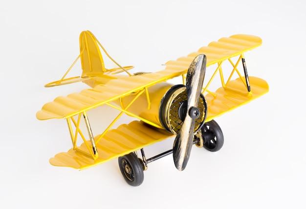 Aereo del giocattolo del metallo giallo dell'annata su priorità bassa bianca