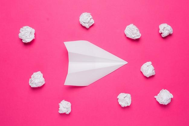 Aereo di carta bianco e palline di carta stropicciata sul rosa