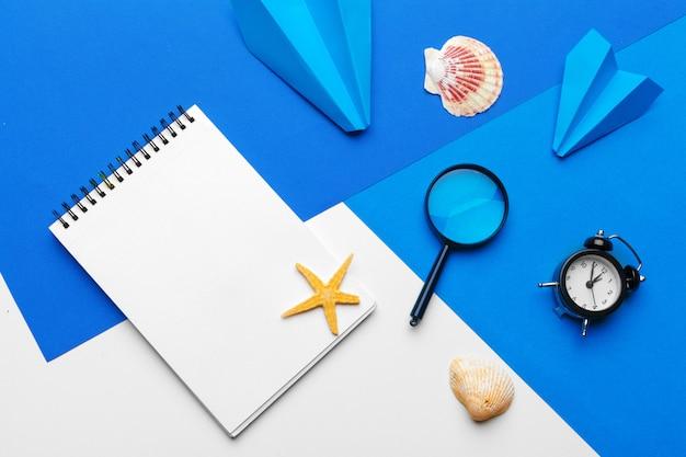 Aereo di carta con articoli per ufficio su sfondo blu