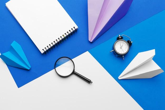Aereo di carta con articoli per ufficio sul blu