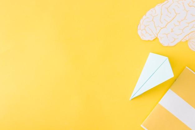 Aereo di carta e cervello con diario su giallo
