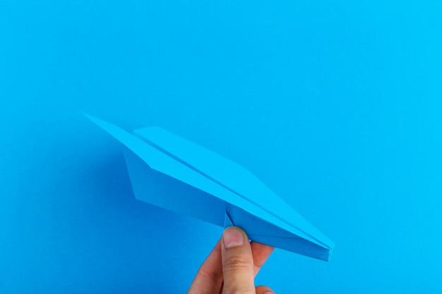 Aereo di carta su sfondo luminoso tenendo in mano umana. viaggi e turismo