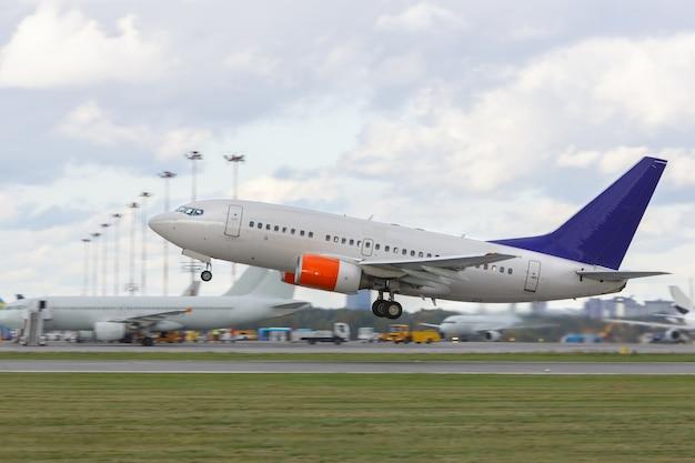 Aereo di linea moderno che decolla dalla pista, aeroplani su fondo, vista laterale.
