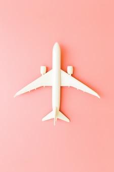 Aereo di modello, aeroplano sul fondo rosa di colore pastello con lo spazio della copia progettazione piana di disposizione.