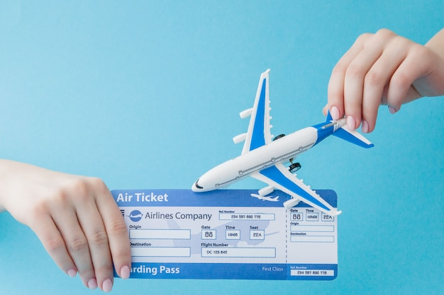 Aereo e biglietto aereo in mano della donna su un blu