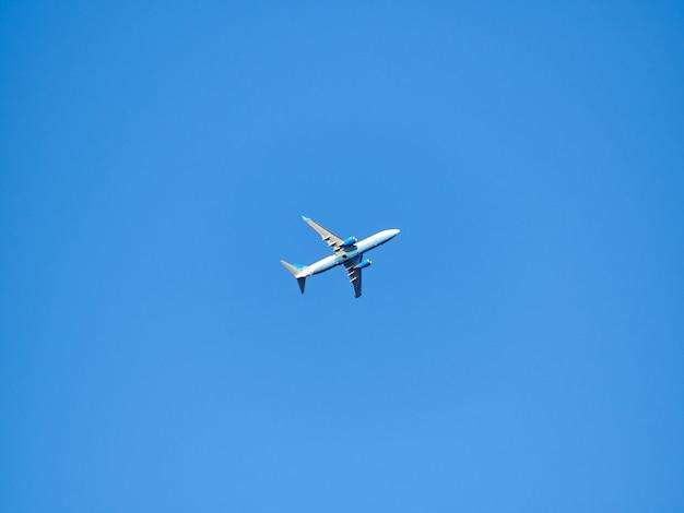 Aereo solo nel fondo blu di minimalismo del cielo soleggiato di giorno