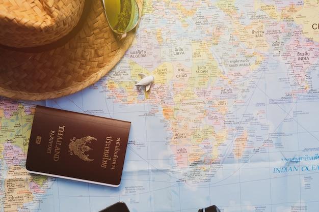 Aeroplano, cappello di paglia e passaporto sulla mappa con effetto luce del sole