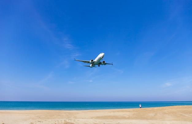 Aeroplano commerciale che atterra sopra il mare e chiaro cielo blu