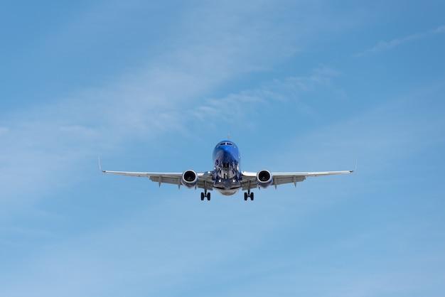 Aeroplano commerciale che vola in cielo blu, flap pieno e carrello di atterraggio esteso