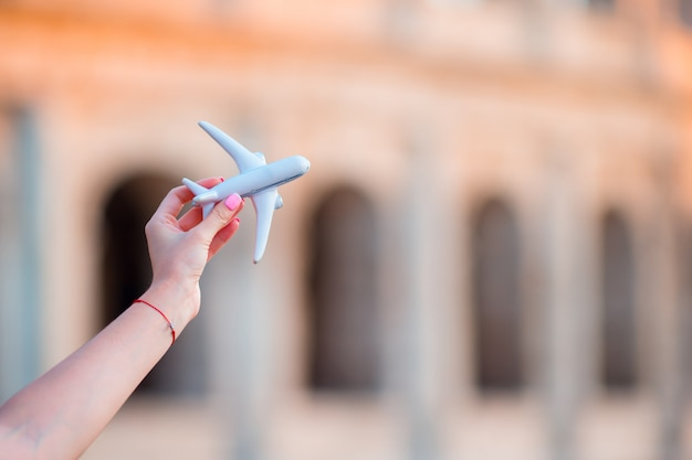Aeroplano del giocattolo del primo piano sul fondo di colosseum. vacanze europee italiane a roma. concetto di immaginazione.