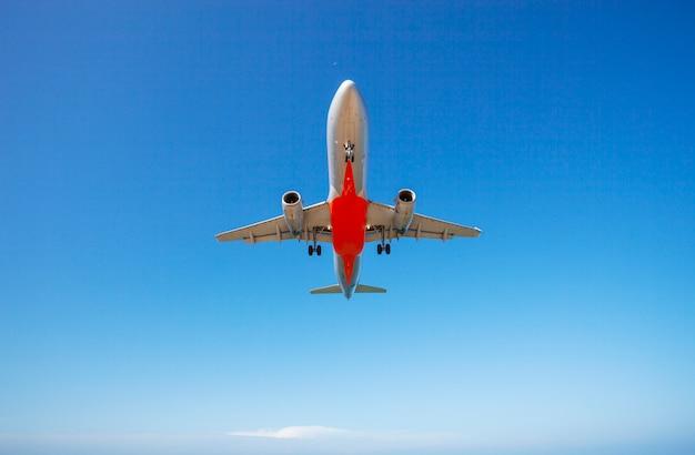 Aeroplano del passeggero che atterra il chiaro cielo blu e il fondo delle nuvole