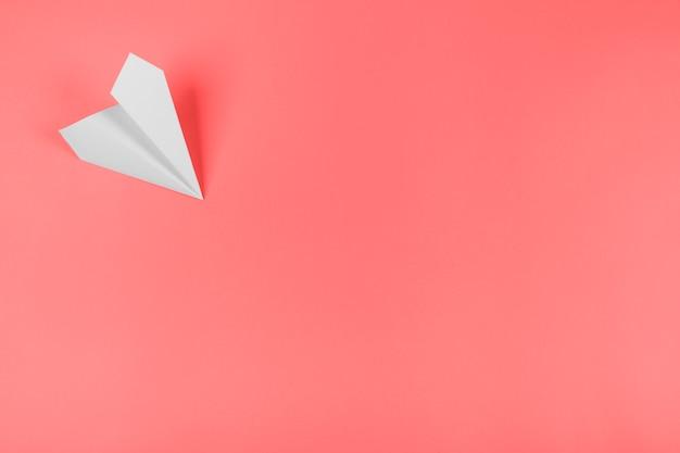 Aeroplano di carta bianca all'angolo dello sfondo corallo