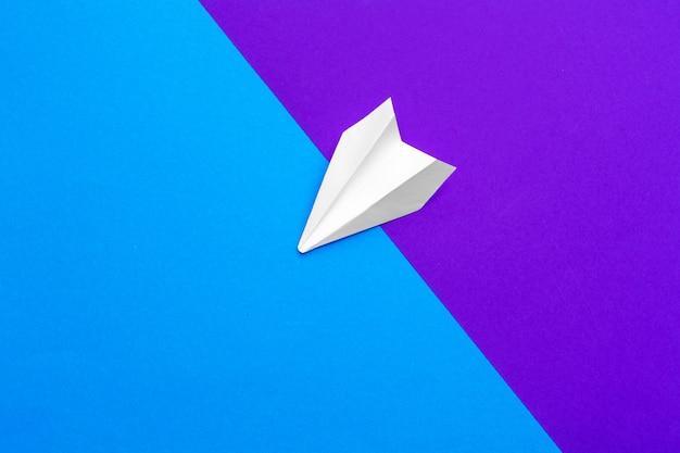 Aeroplano di carta bianco su un blocco di colore blu e viola