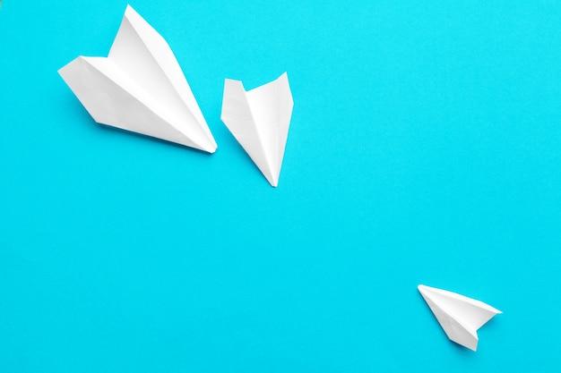 Aeroplano di carta bianco su un blu