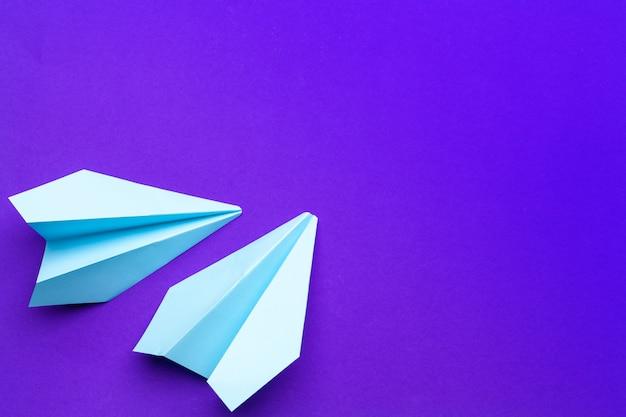 Aeroplano di carta bianco su un viola