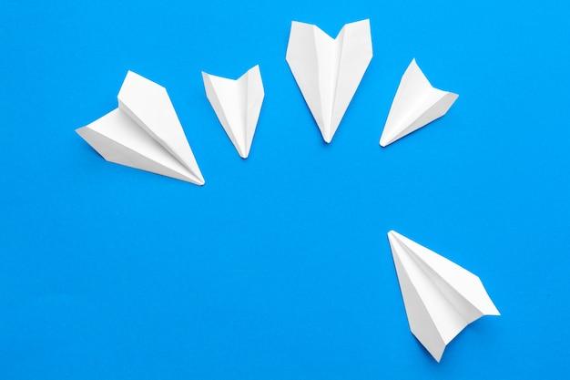 Aeroplano di carta bianco su uno sfondo di carta blu