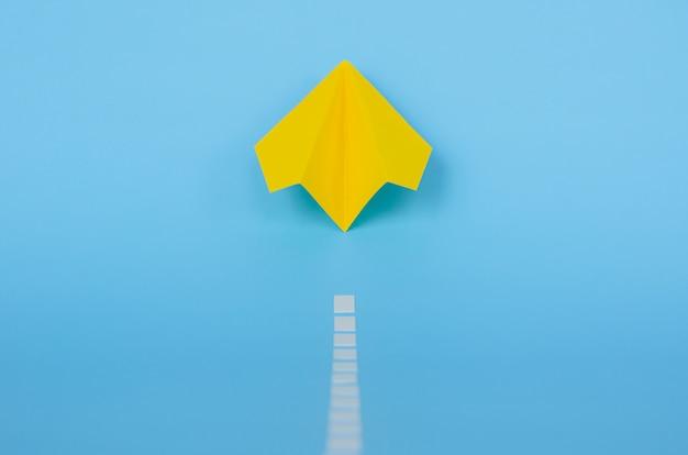 Aeroplano di carta giallo che si alza dalla pista su fondo blu. minimo concetto di viaggio e vacanza.