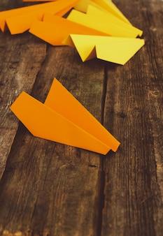 Aeroplano di carte sulla tavola di legno. concetto di viaggio