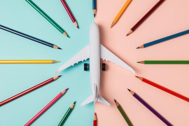 Aeroplano di modello e matita colorata su fondo blu e rosa.