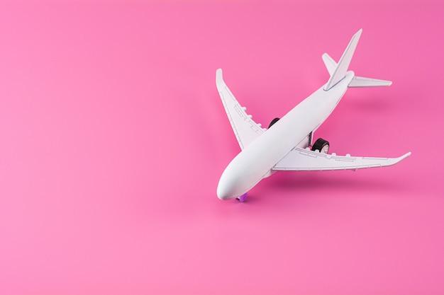 Aeroplano di modello su fondo di carta rosa.