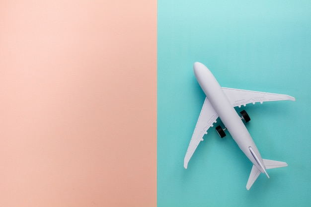 Aeroplano di modello sul fondo di colore pastello rosa e blu.