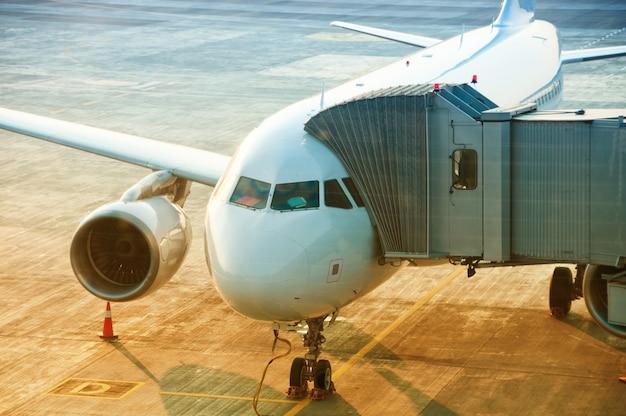Aeroplano in procinto di decollare in aeroporto, ponte d'imbarco passeggeri attaccato al velivolo