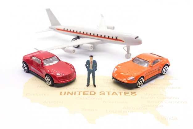 Aeroplano miniatura della gente, dell'uomo d'affari e dell'automobile sulla mappa americana