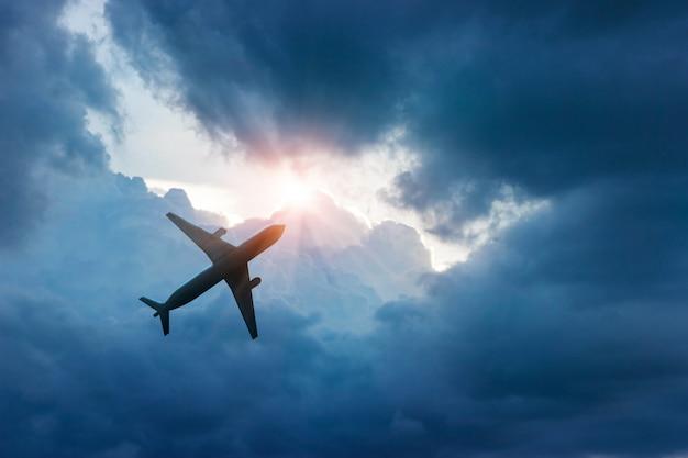 Aeroplano nel cielo e nella nuvola blu scuro
