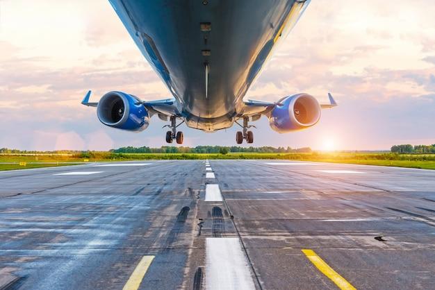 Aeroplano prima dell'atterraggio, vista dal basso dei motori e delle ali, wpp con lanshtafom prima del tramonto