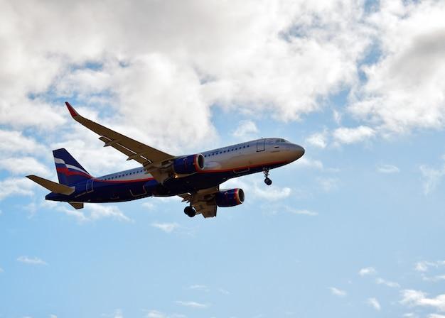 Aeroplano su un cielo blu tra le nuvole