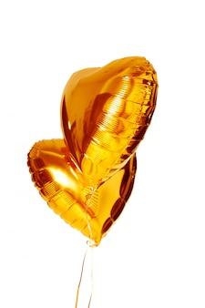 Aerostato metallico del grande cuore dell'oro isolato su bianco