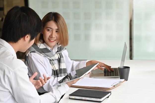 Affare che incontra insieme la compressa digitale in ufficio moderno