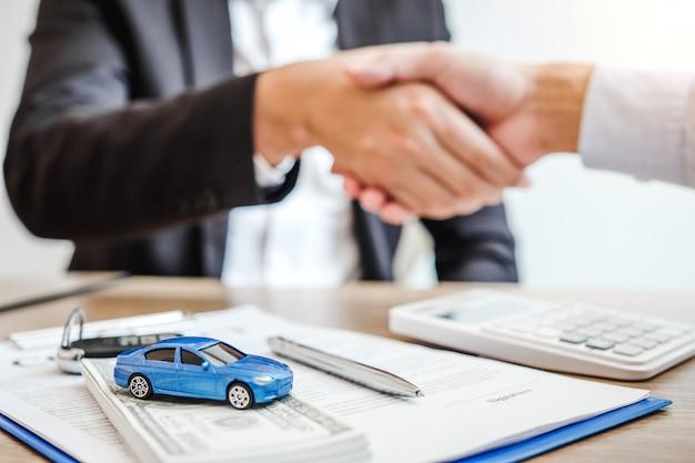 Affare della stretta di mano dell'agente di vendita per concordare il riuscito contratto di prestito dell'automobile con il cliente e firmare il concetto dell'automobile dell'assicurazione del contratto di accordo.