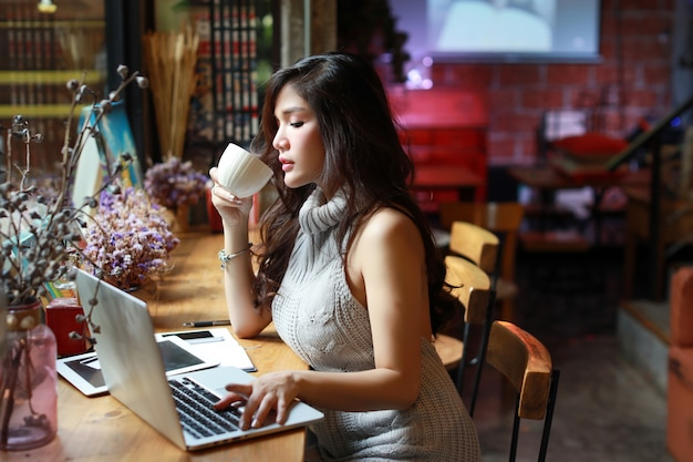 Affare di vista laterale che vende online, giovane donna asiatica in abbigliamento casual che lavora al computer