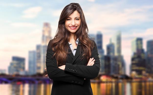 Affare, giovane donna sorridente di affari all'aperto in una regolazione moderna della città
