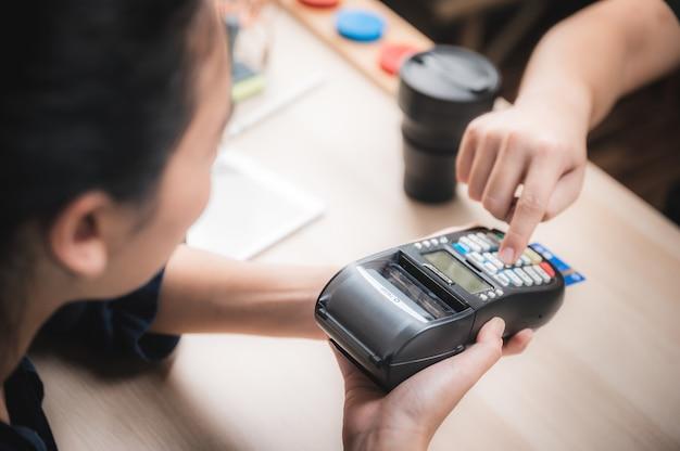 Affari che pagano con la macchina della carta di credito, concetto di pagamento dell'acquisto del cliente