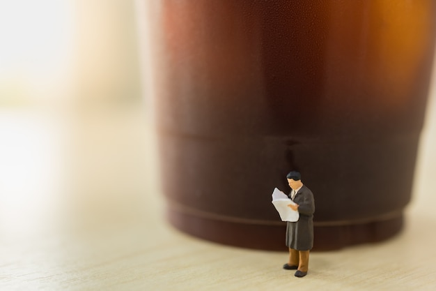 Affari, concetto di rilassamento. chiuda su della figura miniatura della gente dell'uomo d'affari che sta il giornale della lettura con la tazza di plastica asportabile di caffè nero ghiacciato sulla tavola di legno.