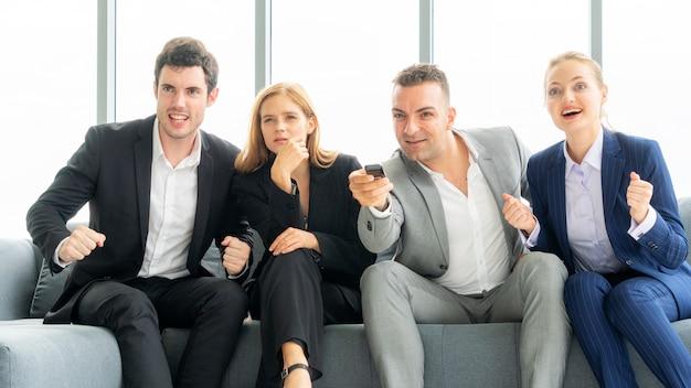 Affari degli amici seduti sul divano eccitanti al programma televisivo. lavoro di squadra vita professionale felice