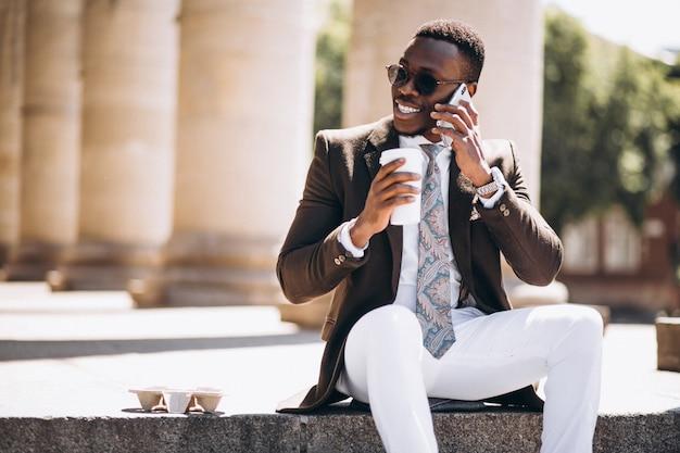 Affari dell'afroamericano con caffè e telefono che si siedono sulle scale di una costruzione
