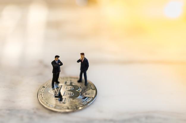 Affari, e-commerce, criptovaluta, finanza e tecnologia. chiuda su della figura miniatura di due uomini d'affari che sta sulla moneta del bitcoin su terra con copyspace.